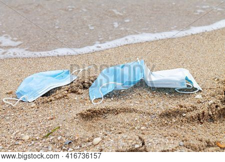 Used Disposable Protective Face Masks Discarded To Ocean. Environmental And Sea Plastic Pollution Co