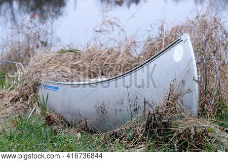 An Old Aluminum Canoe Sitting In Some Tall Grass Beside A Lake.