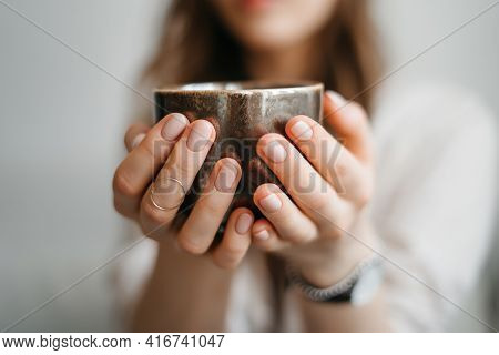 Female Hands Hands Holding Cup Of Tea. Tea Time. Cosy Photo With Blurred Background. Natural Light,