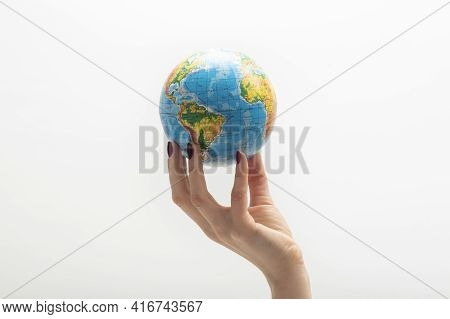 Globe At The Tip Of Woman's Fingers. Female Hand Holds Globe. World In Human Hands. White Background