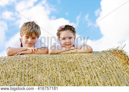 Closeup Of Two Kids Laying On Hay Bale In Wheat Field. Portrait Of German Children During Oktoberfes