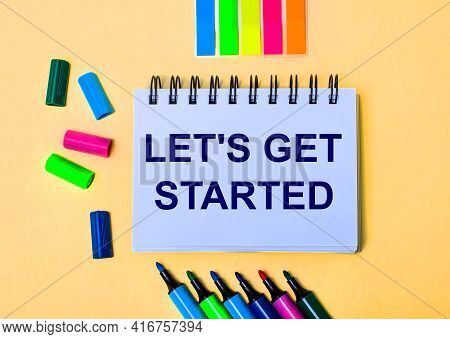 On A Beige Background, A Notebook With The Words Let Is Get Started, Bright Felt-tip Pens And Sticke