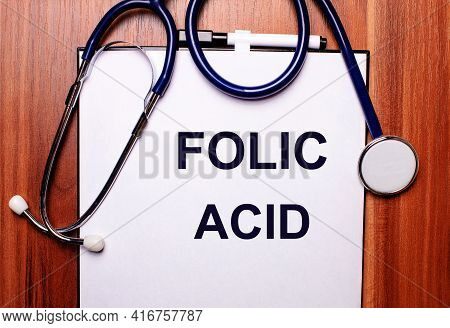 On A Wooden Background Lies A Stethoscope And A Sheet Of Paper With The Inscription Folic Acid. Flat