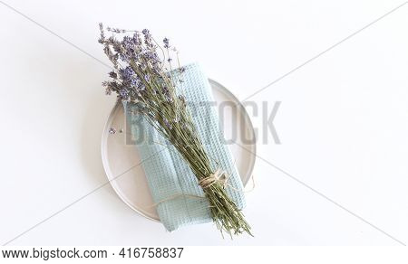 Closeup Of Lavender, Earthenware Plate And Blue Cotton Towel On White Table Background. Floral Compo