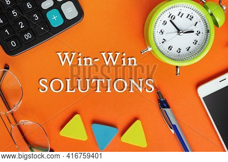 Text Writing Win-win Solutions, Glasses, Alarm Clock, Smartphone, Calculator And Pen On A Bright Ora