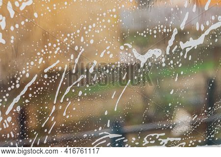 Streaks Of Water And Soap Foam On The Window Pane. The Concept Of Cleaning And Washing Home Windows.