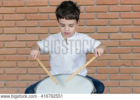 7 Year Old Child Focused On His First Drum Lessons. Brick Wall Background.
