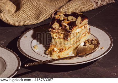 Piece Of Layered Homemade Sponge Cake On A White Saucer With A Spoon And A Linen Napkin, Black Backg