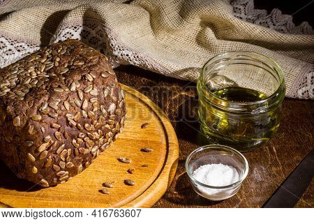 Still Life - Black Bread With Sunflower Seeds, Olive Oil And Coarse Salt In Glass Jars, A Knife, And