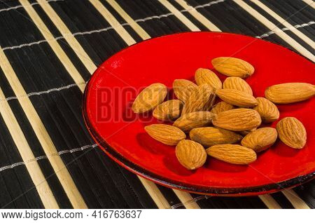 Almonds Nuts In A Red Saucer On A Bamboo Mat, Closeup