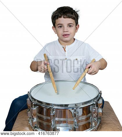 7 Year Old Child Staring At The Camera And Playing The Drums. White Background.