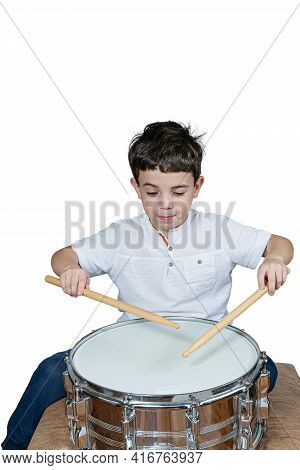 7 Year Old Kid Playing The Drums And Making A Funny Face. White Backgrond.