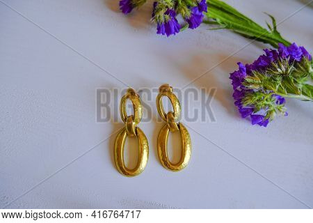 Golden Elegant Earrings On White Wooden Background Across Purple Statice Flowers. Top View. Copy Spa