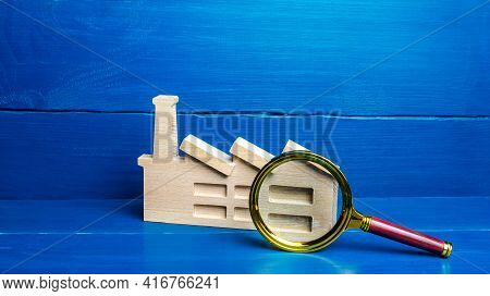 Figurine Of An Industrial Factory Plant And A Magnifying Glass. Big Business Monitoring Concept, Emi