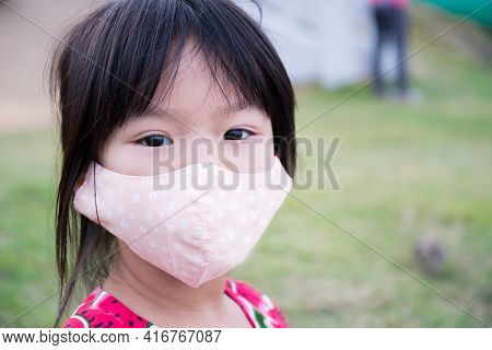 Close Up A Cute Girl Face Wearing An Orange Cloth Face Mask. Child Are Sitting In The Park. Kid Wear