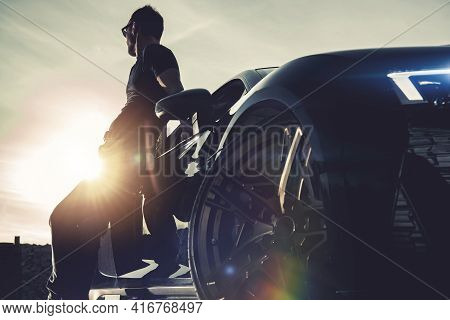Successful Men And His Luxury Exotic Car. Summer Time Road Trip And Sunset Scenery. Moren Automotive