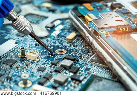 Technician Repairing Inside Of Hard Disk By Soldering Iron. Integrated Circuit. The Concept Of Data,