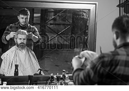 Side View Of Serious Man With Stylish Modern Haircut Looking Forward In Barbershop.
