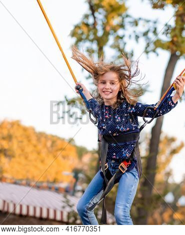 Smiling little girl jumping on trampoline jumping rope in autumn adventure park