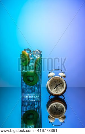 A Glass Of Water With Ice And Slices Of Kiwi Standing On A Mirror Table In Neon Light. Body Detoxifi