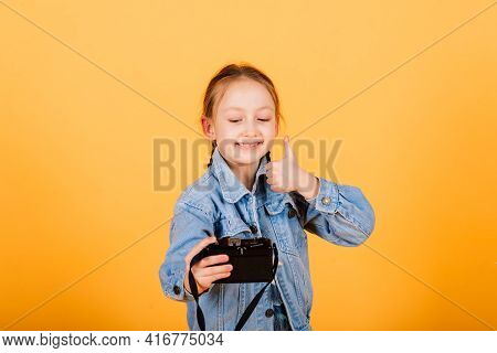 Child With Camera. Little Girl Photographing In Studio