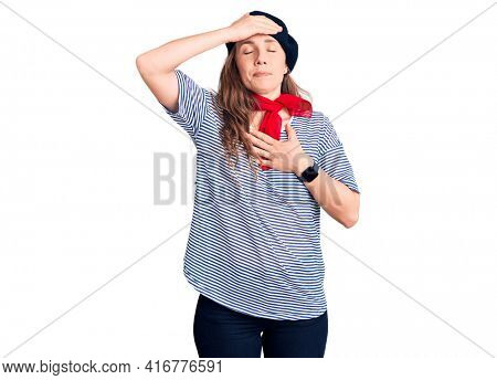 Young beautiful blonde woman wearing french beret and striped t-shirt touching forehead for illness and fever, flu and cold, virus sick