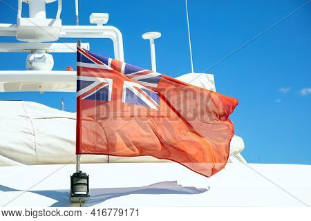 Uk Flag On Pole On Ferry's Stern. Ongoing Cruise To Islands. Blue Sky Background