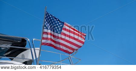 Usa Flag On Pole On Ferry's Stern. Ongoing Cruise To Islands. Blue Sky Background