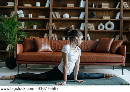 Profile View Of Young Afro American Woman In Sportswear Stretching Legs, Doing Splits Sitting On Flo