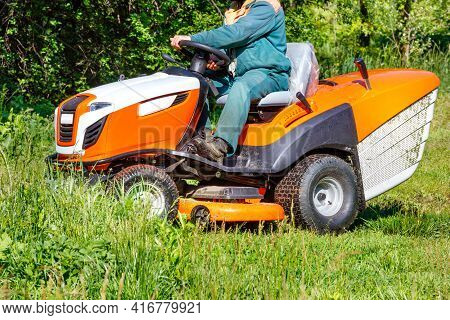 A Gardener Sitting At A Professional Tractor Lawn Mower Mows Tall Green Grass In An Overgrown Meadow