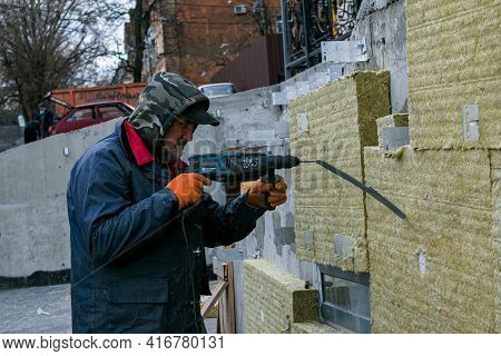 Dnepropetrovsk, Ukraine - 06.04.2021: A Man Installs A Layer Of Thermal Insulation On The Wall Of Th