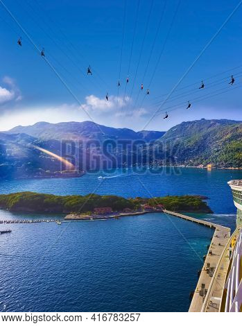 People Flying At High Zipline On Caribbean At Labadee Island At Haiti. The Arial View From Desck Of