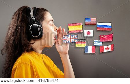 Online Language Learning. Portrait Of A Young Woman Wearing Headphones, Her Hand Over Her Open Mouth