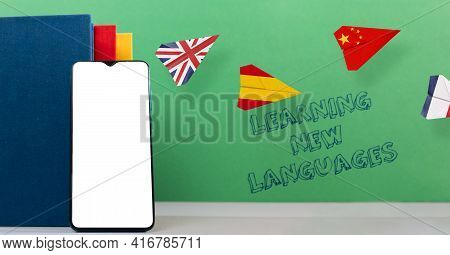 Cellphone Apps For Learning Foreign Languages. A Smartphone, Book And Paper Airplanes With Spanish,