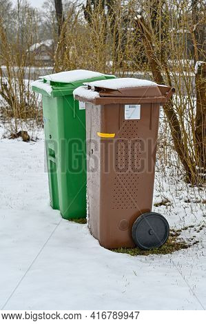 Garbage Bins In Brown And Green And Snow