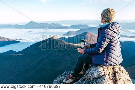 Young Hiker Female Sitting On The Mountain Summit Cliff And Enjoying Mountains Valley Covered With C