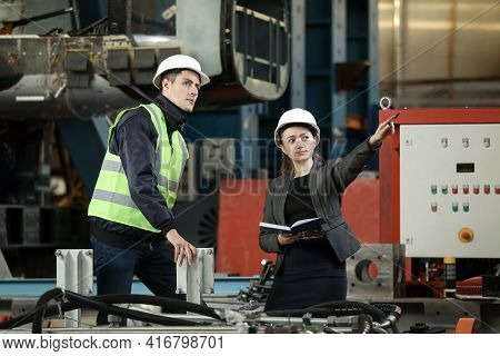 Portrait Of A Female Factory Manager In A White Hard Hat And Business Suit And Factory Engineer In W