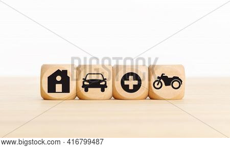 House, Car, Health And Bike Icons On Wooden Blocks Types Of Insurance Concept. Copy Space