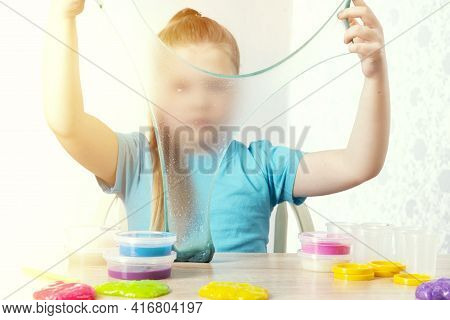 A Blonde Child Is Playing With A Slime. Little Beautiful Caucasian Girl Is Playing With Many Slimes.