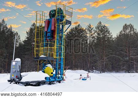 Vertical Oil Pump Jack Winter Working. At The Orange Sunset Dawn Of The Sky With Clouds. Oil Rig Ene