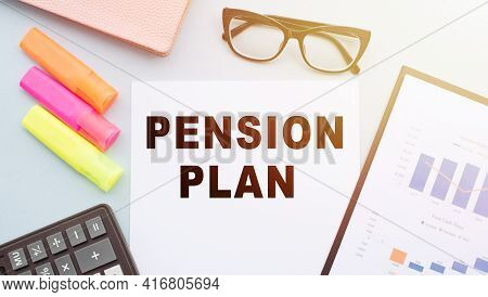 The Text Pension Plan On Office Desk With Calculator, Markers, Glasses And Financial Charts.