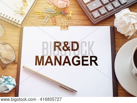 On A Wooden Table There Is An Office Sheet Of Paper With The Text R And D - Manager Research And Dev