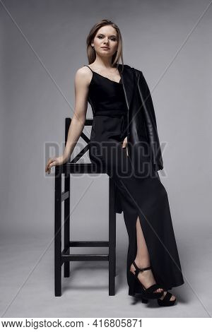 A Young Woman In A Black Jumpsuit Sits On A Chair And Looks At The Camera.