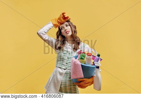 A Tired Female Cleaner Holds A Bucket Of Tools For Cleaning A House Or Hotel.