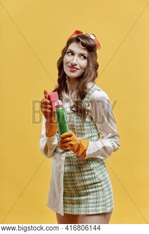 A Young Female Cleaner Holds Tools For Cleaning The House. Pin-up Style.
