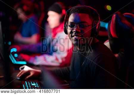 Neon Light In The Arena At The Online Shooter Tournament. A Young Black Cyber Athlete Looks At The C