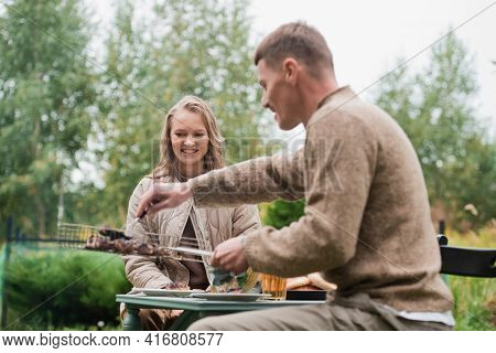 A Young Man Is Courting His Fiancee. He Puts Chunks Of Grilled Meat From The Barbecue Grill On Her P