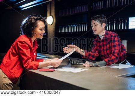 Two Young Beautiful Girls Are Busy Choosing Tattoos From Sketches On A Laptop And Paper In A Tattoo