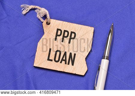 Top View Of Pen And Wooden Board Written With Ppp Loan. Business Concept.