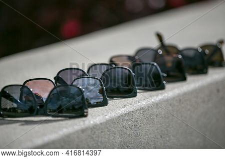 Men's Sunglasses Of Various Shade Lined Up On A Concrete Wall